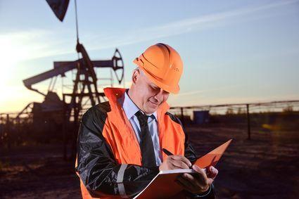 Oil worker in orange uniform and helmet en de background the pump jack and sunset sky.